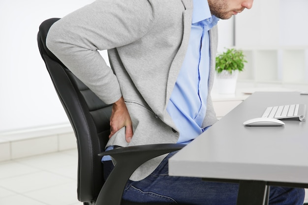 オフィス、クローズアップの肘掛け椅子に腰痛のある男