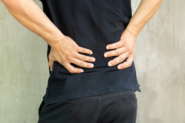 Man with back pain isolated on grey background.