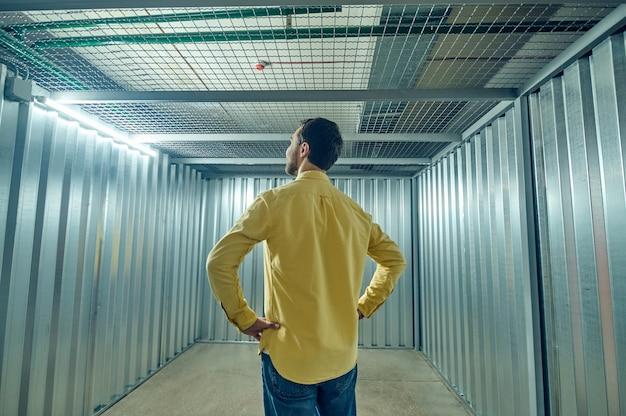 Человек спиной к камере в пустом железном гараже