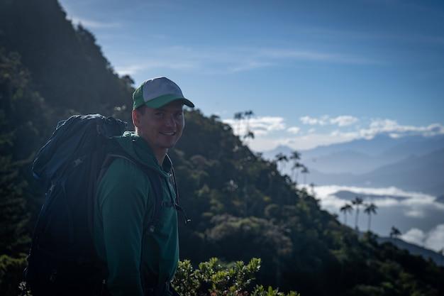Человек с рюкзаком и тропическим видом на горы. концепция путешествий и приключений.