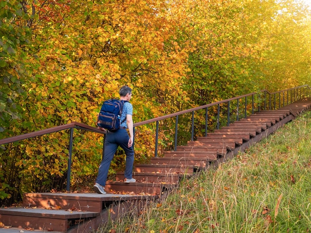 A man with a backpack climbs the eco trail in autumn