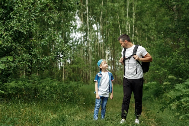 A man with a backpack, a father and his son on a hike, walking during walks in the woods.