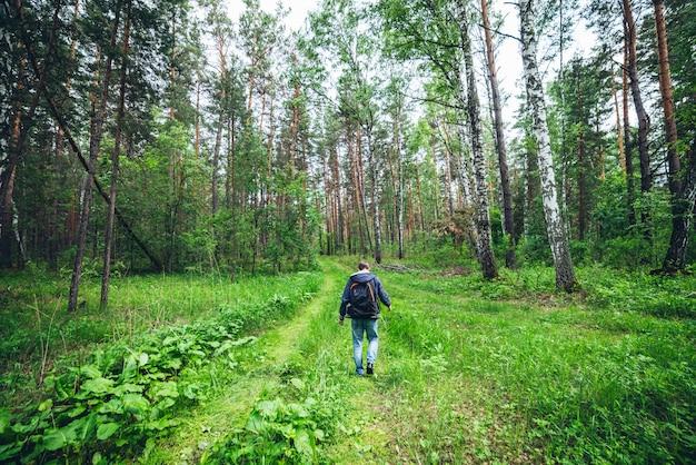 Человек с рюкзаком в лесу.