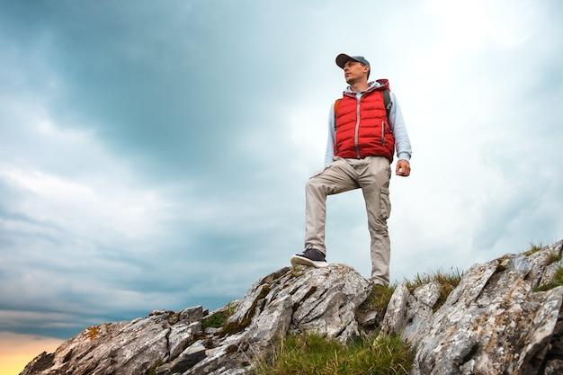 バックパックを持った男が山の上に立っています。
