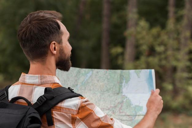 Человек с рюкзаком, глядя на карту во время кемпинга