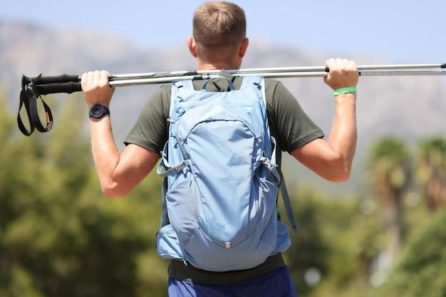 山を見て、彼の手の後ろのビューで杖を持っているバックパックを持つ男
