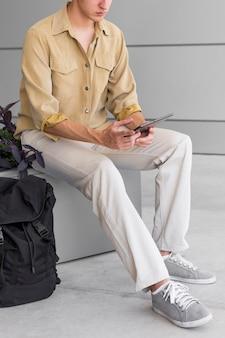 Человек с рюкзаком, глядя на планшет на открытом воздухе