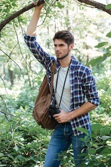 木の近くにバックパックを持つ男