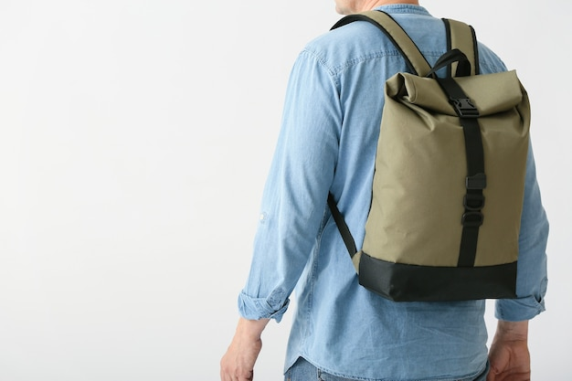 白い表面にバックパックを持つ男