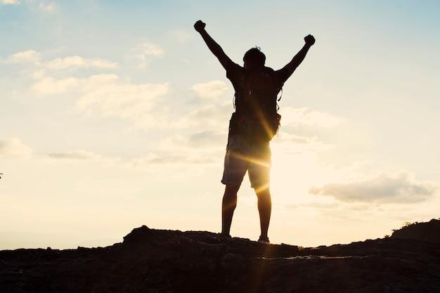 日没時に鞄を手にして崖に立っている男