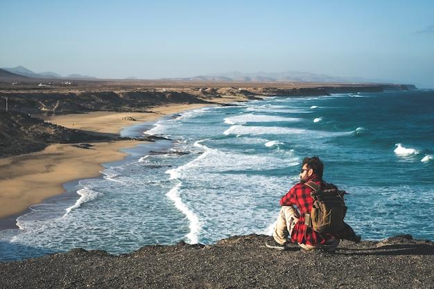 バックパックを持った男が崖の上に座って、大きな海の波のある空の野生のビーチを楽しんでいます