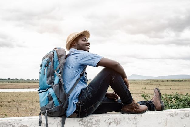 Человек с рюкзаком сидит на каменном заборе