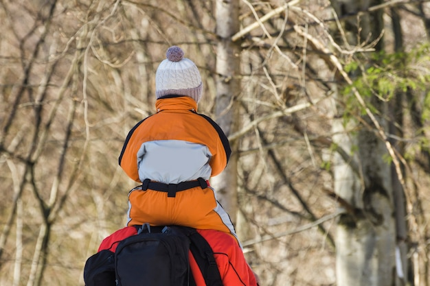 Man with backpack and son on shoulders stands