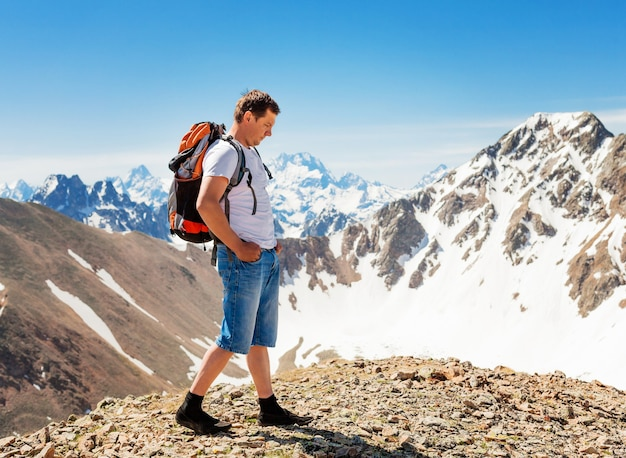 A man with a backpack stands on top of a mountain. mountains of karachay-cherkessia. mountain landscape
