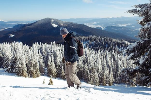 Человек с рюкзаком, походом в горы. холодная погода, снег на холмах. зимний поход. приближается зима, первый снегопад. концепция путешествия, отдыха, релаксации