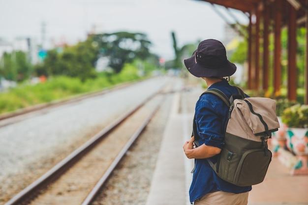 鉄道を離れて歩いてバックパックを持つ男と忍耐力を強調し、目標に向かって前進しようとしている調査。