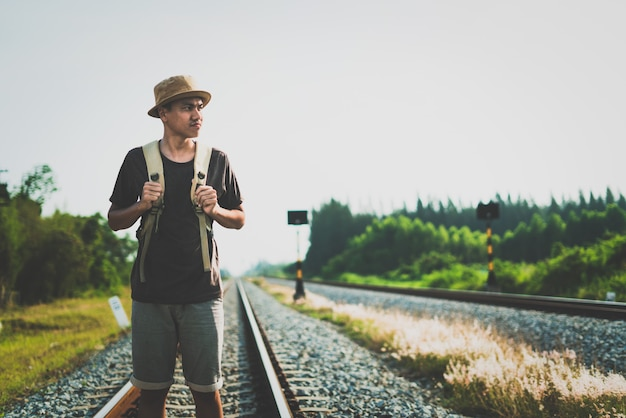 Man with backpack walking away on railroad and emphasize to patience and survey trying step forward to goal