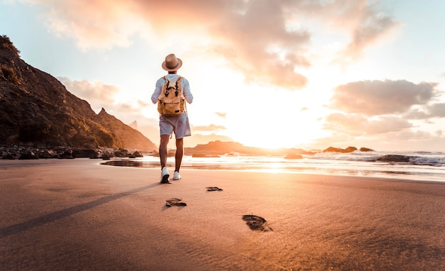 Man with backpack walking on the beach at sunset