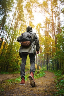 A man with backpack walks in the amazing autumn forest.