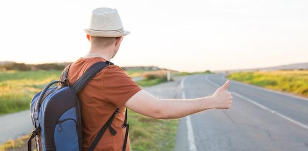 캐주얼 여행복 차림으로 배낭을 메고 길을 따라 걷는 남자, 도로 히치 하이킹. 고속도로 히칭에 서 있는 여행자