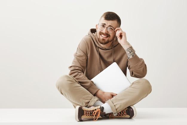 Uomo con cattiva vista guardando più da vicino in bicchieri, seduto con il computer portatile sul pavimento