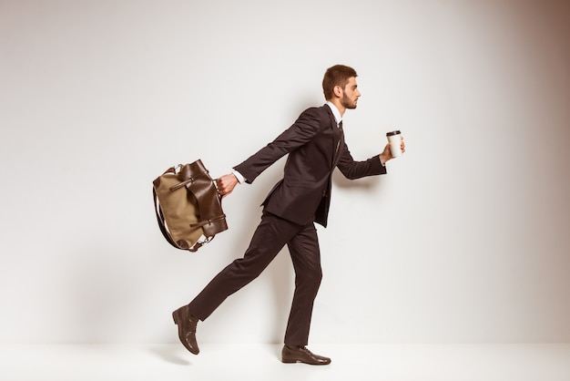 Man with bag and coffee in hands
