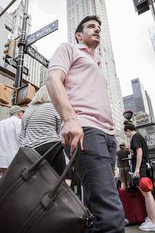忙しい通りに立っている鞄を持つ男