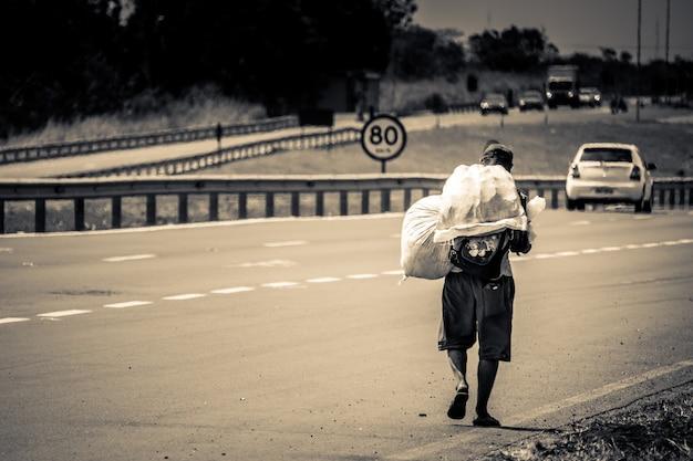 通りを歩いて背中にバッグを持つ男