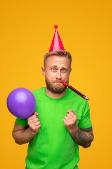 Человек с рожком партии дует воздушный шар
