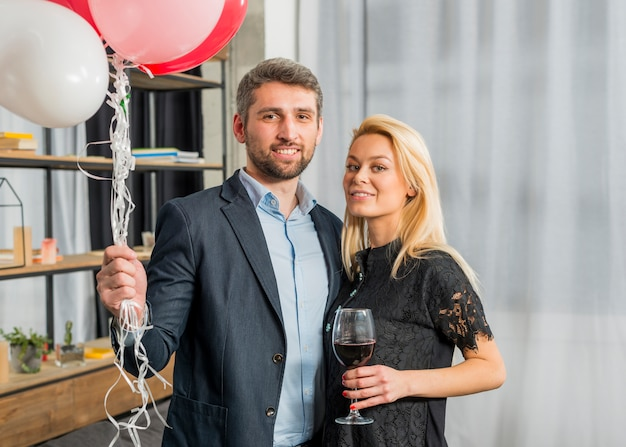 Man with balloons near woman with glass of wine in room