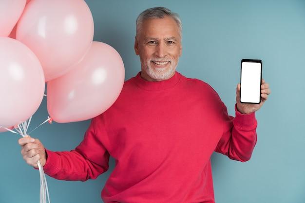 Человек с воздушными шарами в ярком пуловере позирует на синей стене