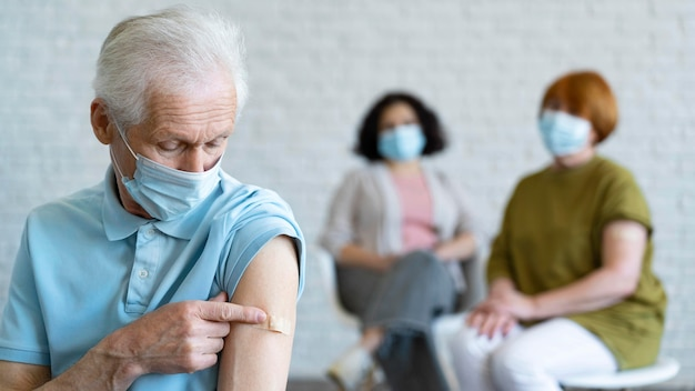 Man with bandage on arm after vaccination