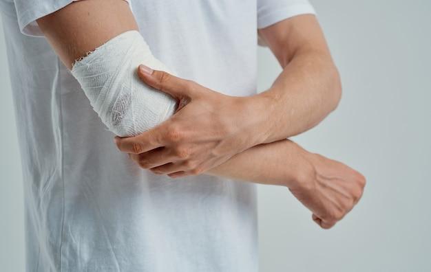 Человек с перевязанным локтем и лекарством от травмы пальца