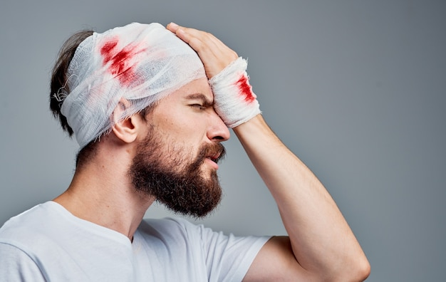 Man with bandaged head and arm blood treatment injury hospital