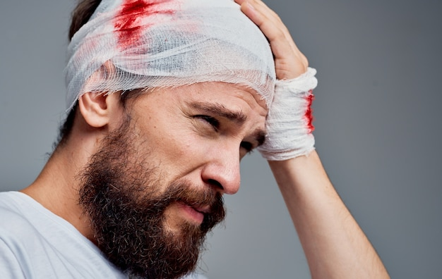 A man with a bandaged head blood resuscitation surgery model gauze on his arm