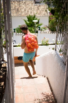 A man with a bare-chested bears a bag of oranges