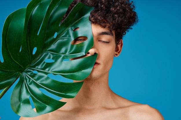 裸の肩の化粧品スキンケア青い背景を持つ男