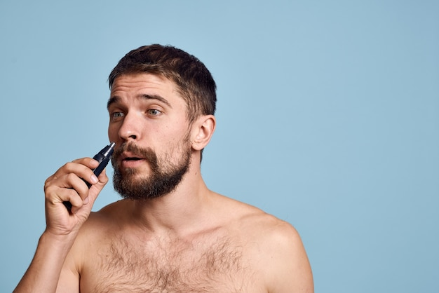 Man with bare shoulders removes nose hair care on a blue background