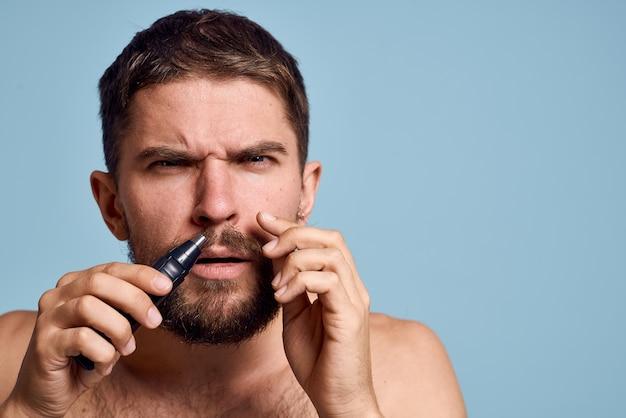 裸の肩を持つ男は鼻毛を取り除きます