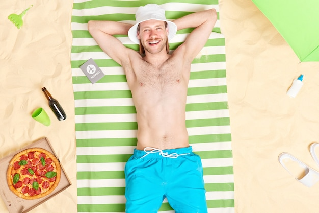 Man with bare torso keeps hands behind head lies on green striped towel travels abroad for vacation eats delicious pizza wears sun hat blue shorts being in good mood