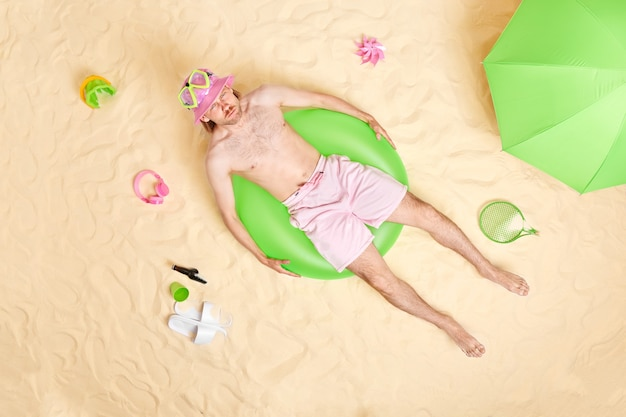 Man with bare torso lies on inflated green swimring surrounded by beach accessories poses on white sand has angry expression sunbathes alone