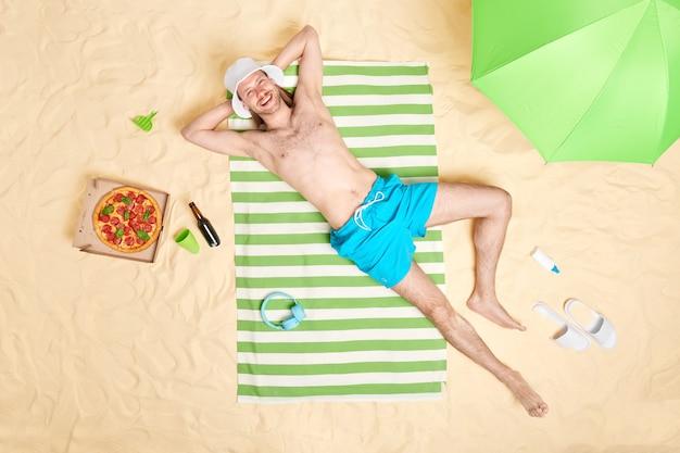 Мужчина с обнаженным торсом с удовольствием носит шляпу от солнца и синие шорты, позирует топлес на полосатом полотенце в окружении пляжных аксессуаров, у него ленивый день, чтобы хорошо отдохнуть на берегу моря. концепция летнего времени