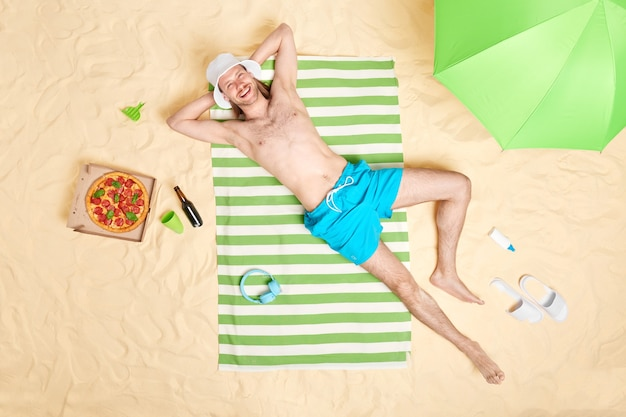 Man with bare torso smiles gladfully wears sunhat and blue shorts poses topless on striped towel surrounded by beach accessories has lazy day good rest at seaside. summer time concept