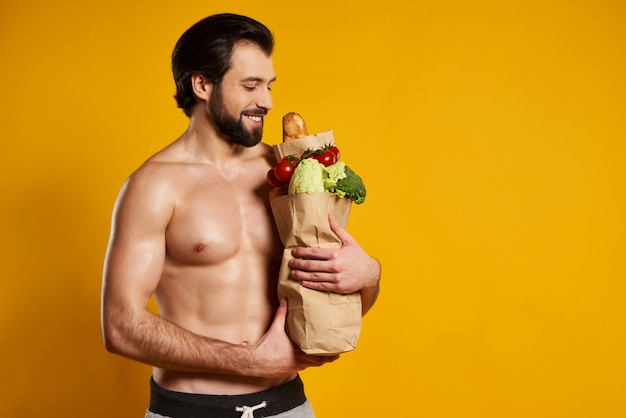Man with bared torso holds paper bag with healthy food.