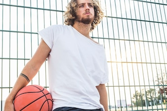Man with basketball standing in front of fence