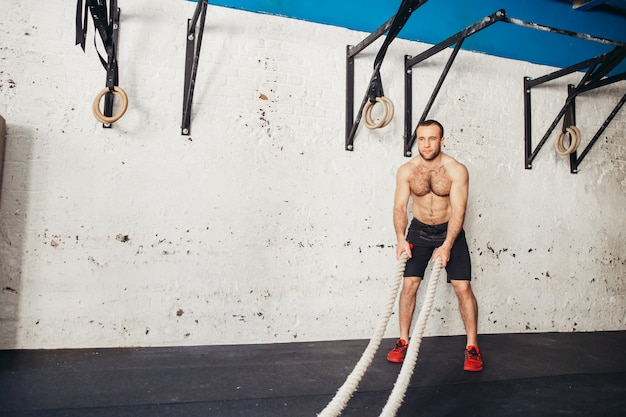 Man with battle ropes exercising in fitness gym