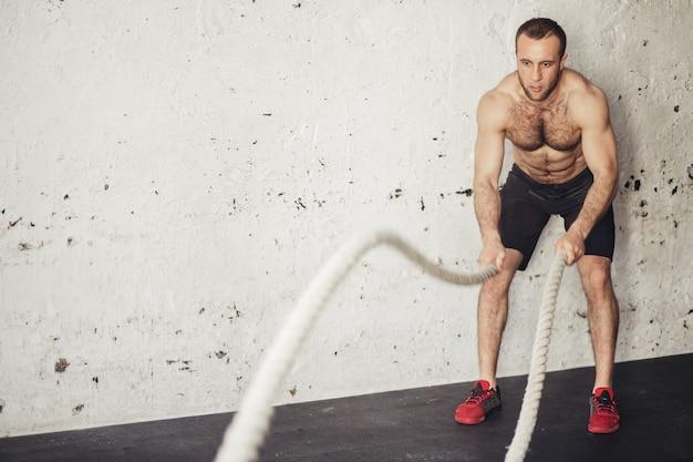 フィットネスジムで運動バトルロープを持つ男