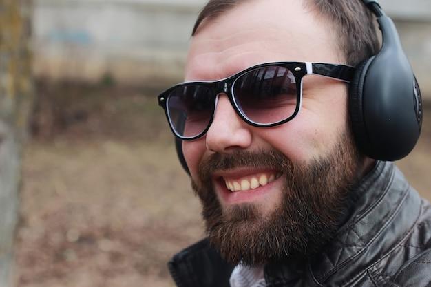 Человек с бородой и наушниками в парке