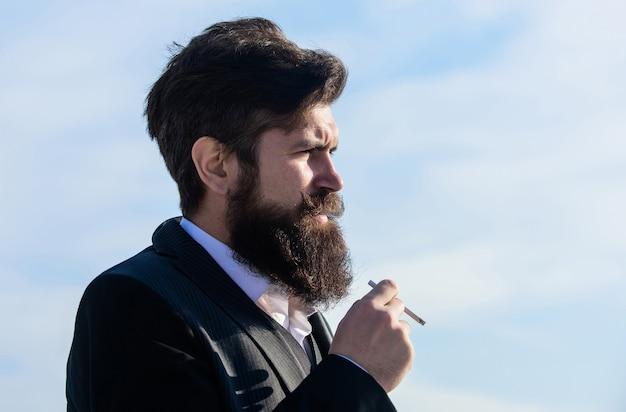 あごひげと口ひげを持つ男がタバコを持っています。ひげを生やしたヒップスター喫煙タバコ青空の背景。タバコを持った男はニコチンの影響を楽しんでいます。喫煙の喜びとニコチン中毒についての真実。