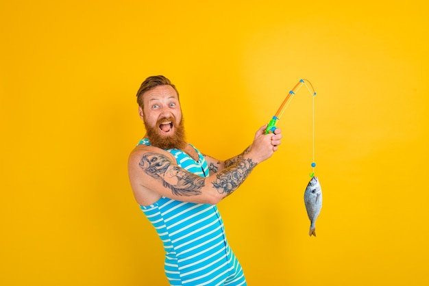 수염과 수영복을 입은 남자가 물고기를 잡았습니다.
